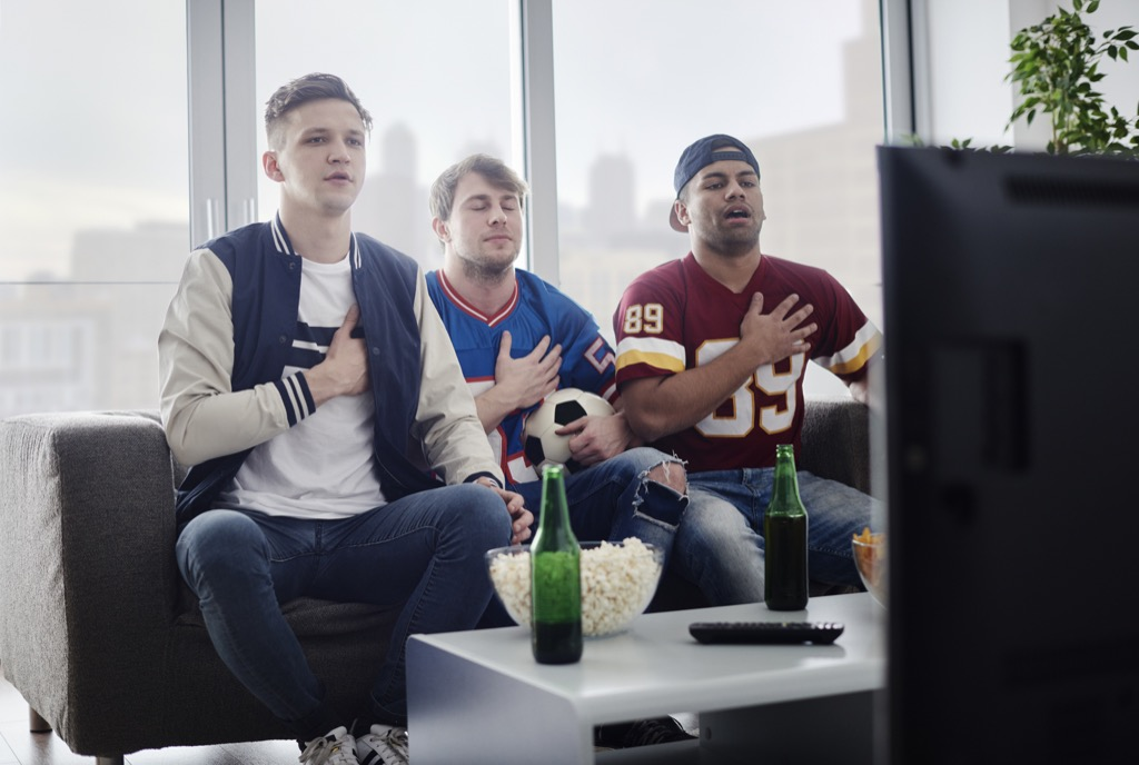 bros watching football and singing along to the star spangled banner