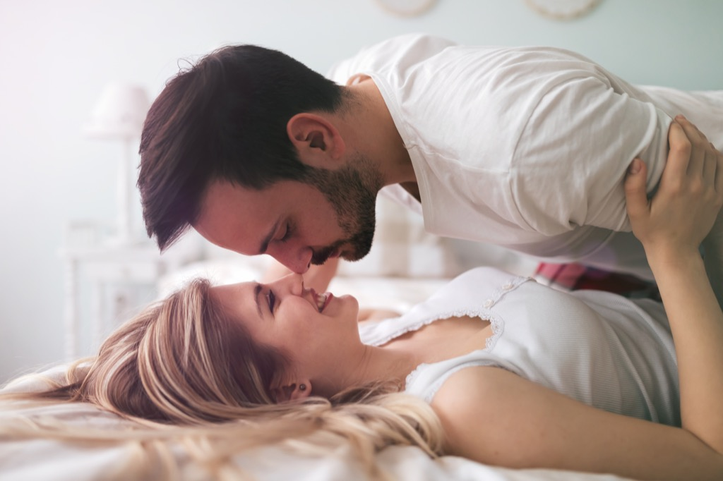 couple kissing on bed, signs your husband is cheating