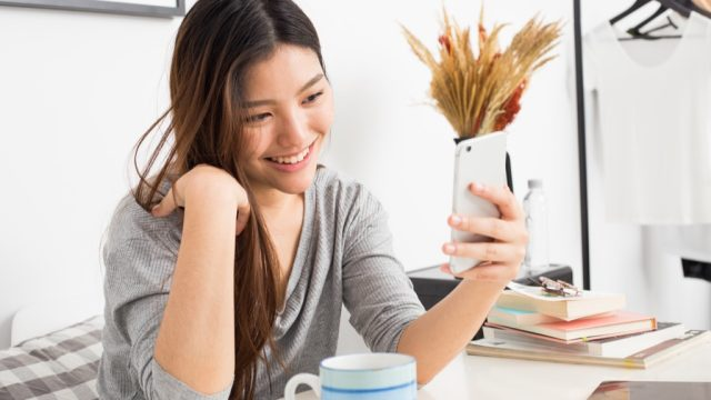young asian woman looking at her phone and smiling