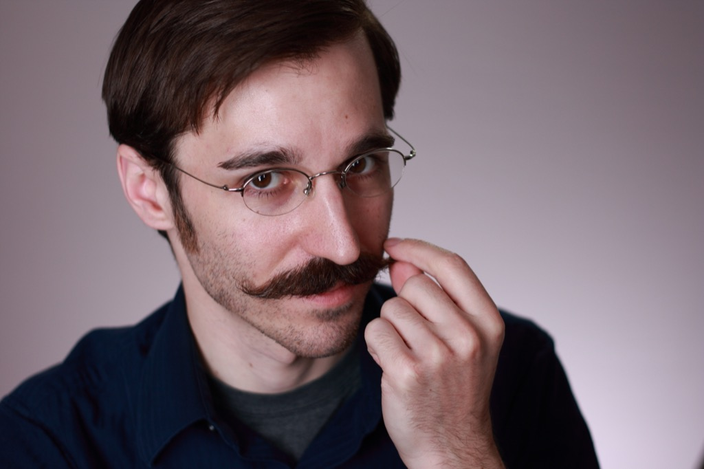 White man with brown hair and glasses touches his handlebar mustache, signs he's lying