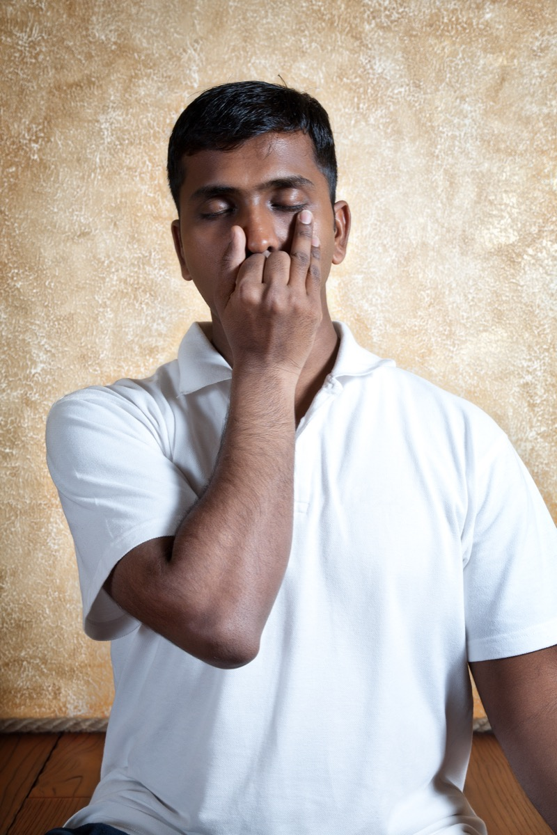 Man holds nostril to stay calm, breathes deeply
