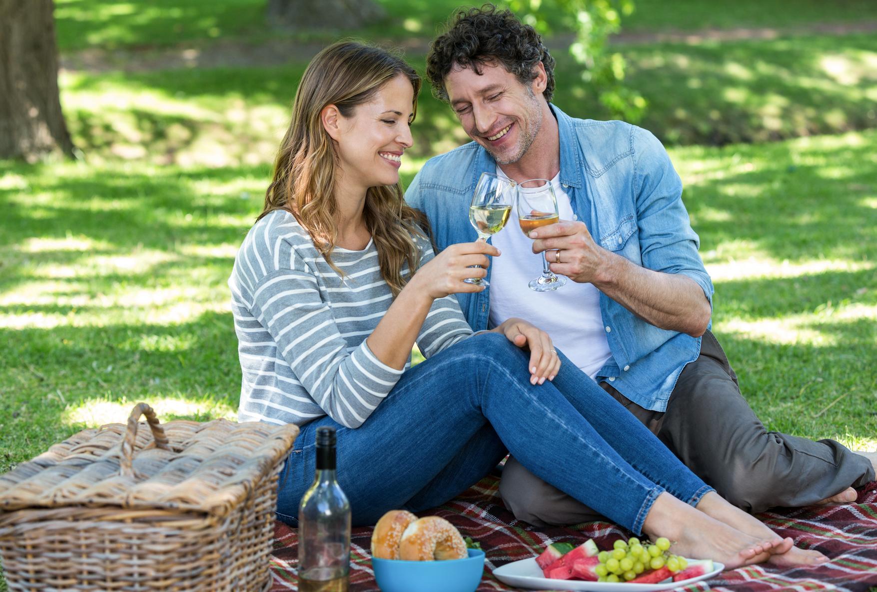 Man and woman having romantic park picnic date