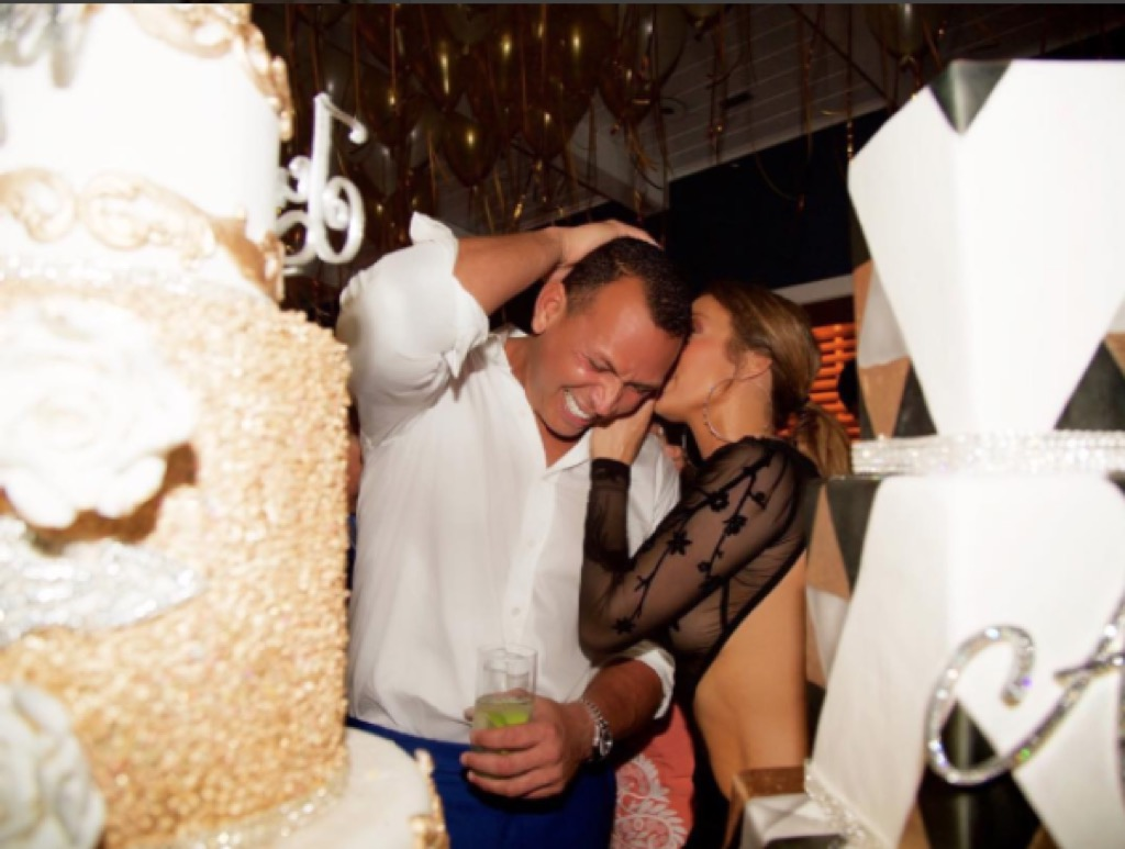 Jennifer Lopez and Alex Rodriguez smiling at a party.