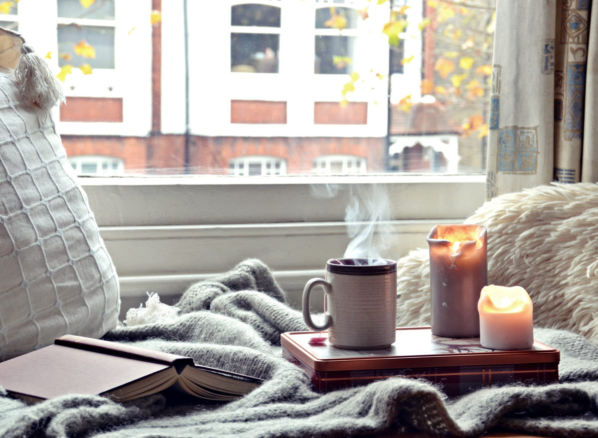 candle burning by window sill with cup of steaming hot coffee