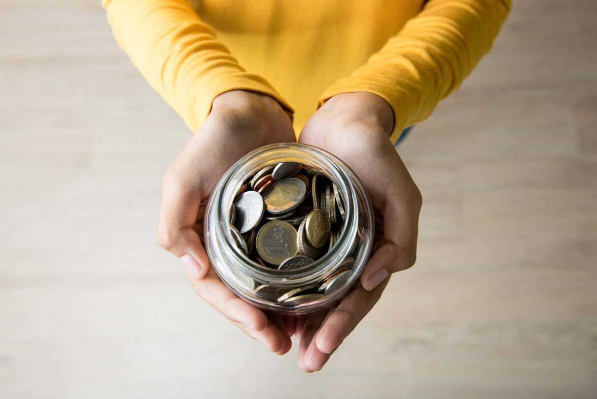 person's hands holding out a jar of change