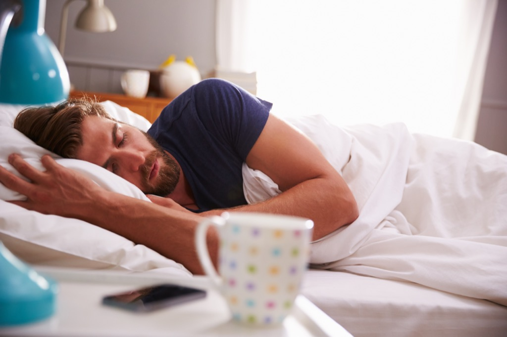 Man in bed sleeping, showing why you want to cut out coffee before bed. It's bad for your body clock.