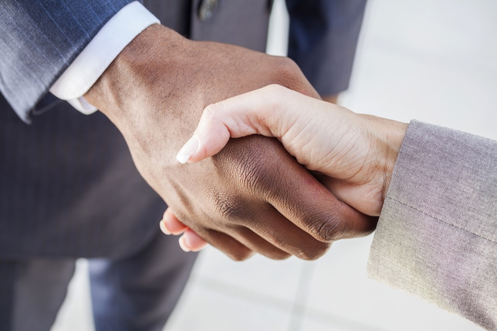 black person and white person shake hands, office etiquette that's outdated