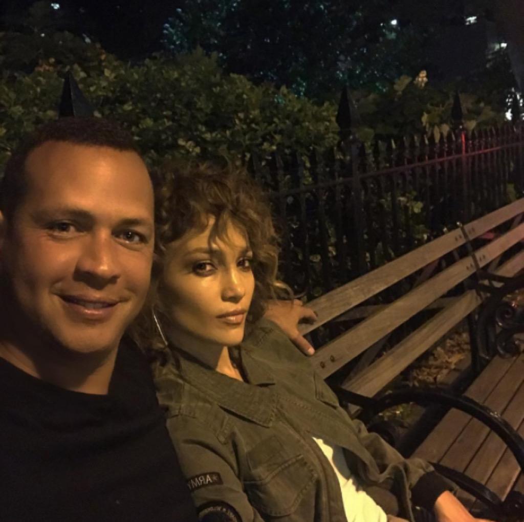 Alex Rodriguez and Jennifer Lopez on a park bench.