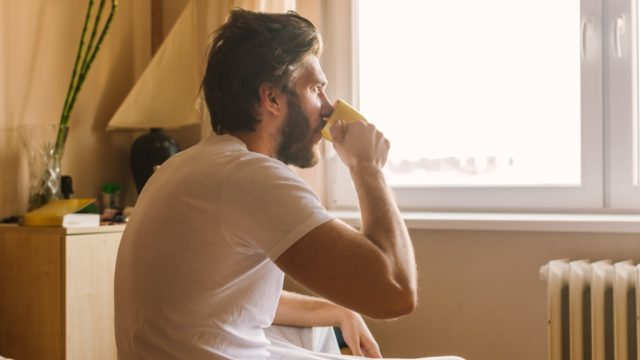 man drinking coffee in bed, things you should clean every day