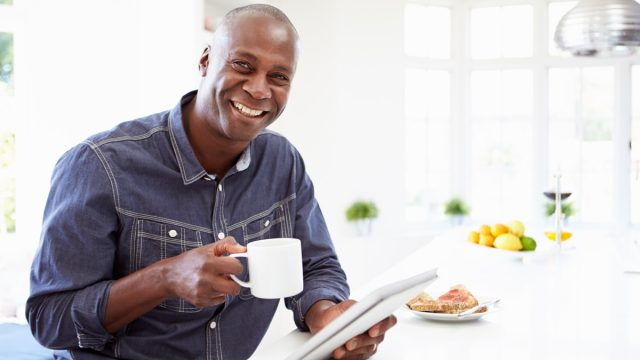 man holding coffee smiling with breakfast