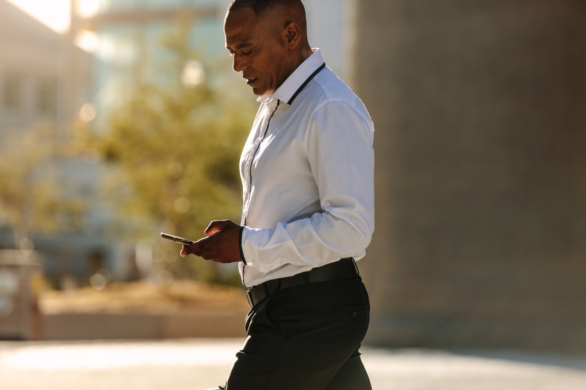 Black Man Looking at his Phone while he Walks to Work Healthy Man