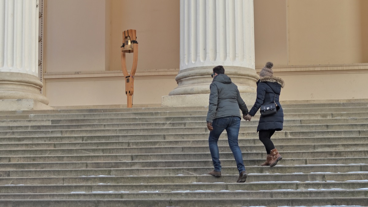 Man and woman holding hands and walking up museum steps