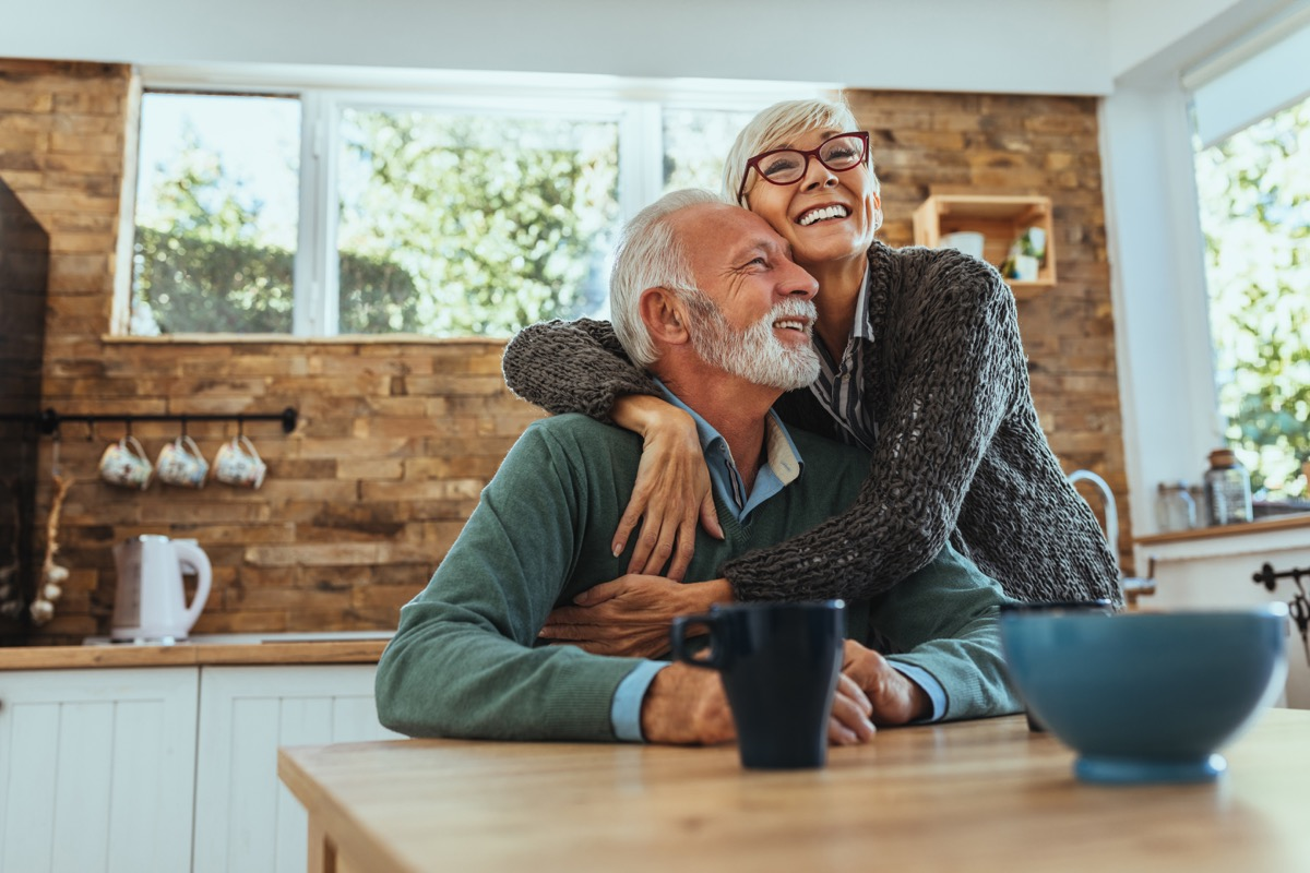 older couple hugging and smiling in the kitchen