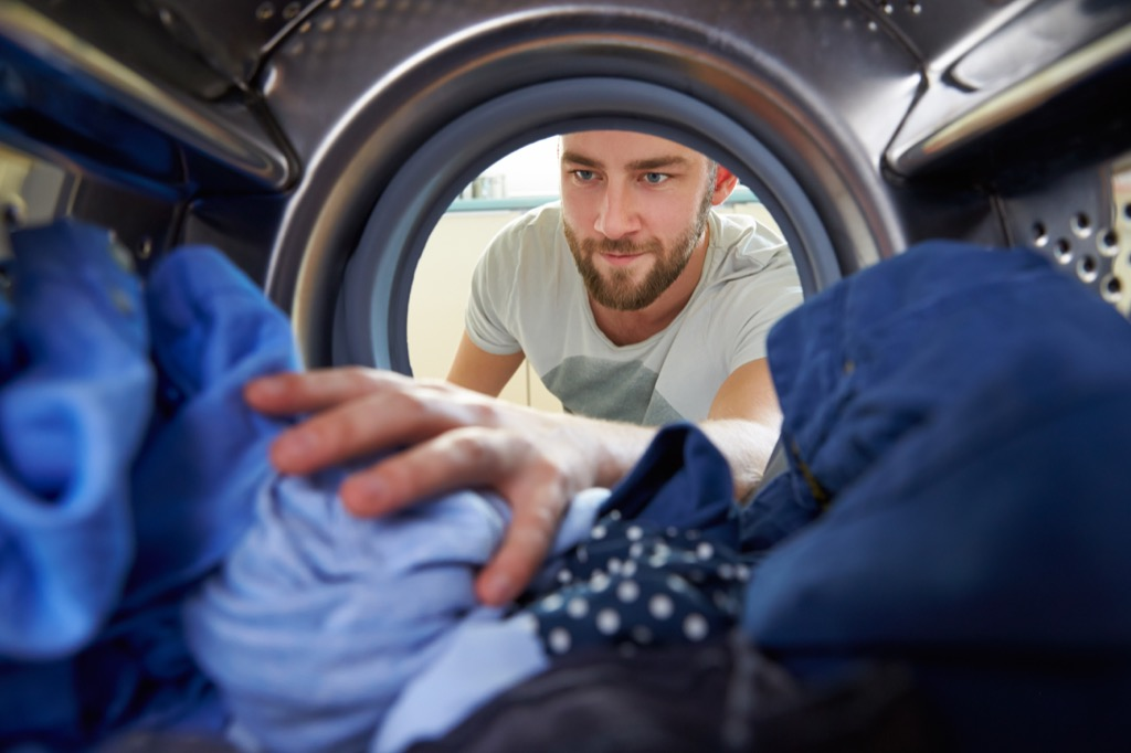 Man Doing Laundry Ways You Ruin Clothing