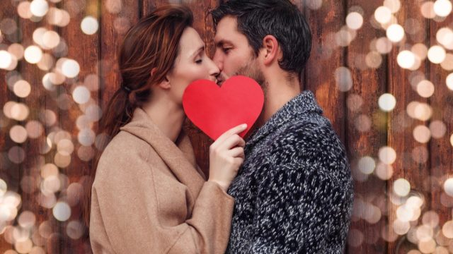 couple kissing behind a heart - signs you're in love