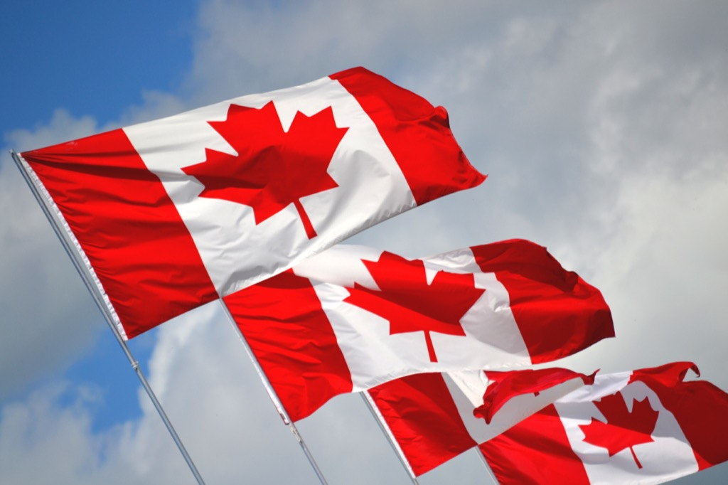 Canadian flags flying in sunny sky
