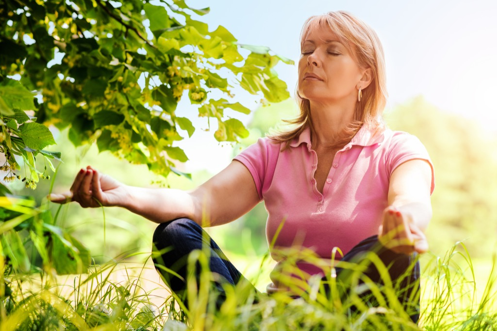 older woman meditating in grass, ways your body changes after 40