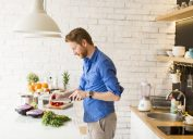 man in blue button down shirt cooking food in modern kitchen