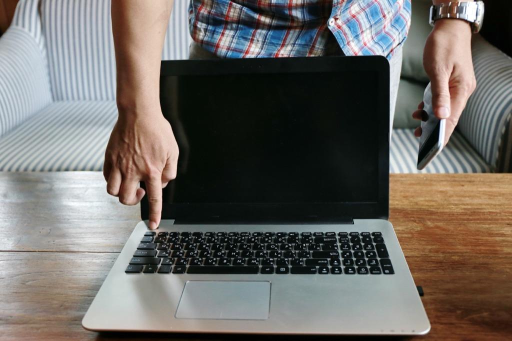 Man Powering on a Laptop Get Rid of Old Stuff
