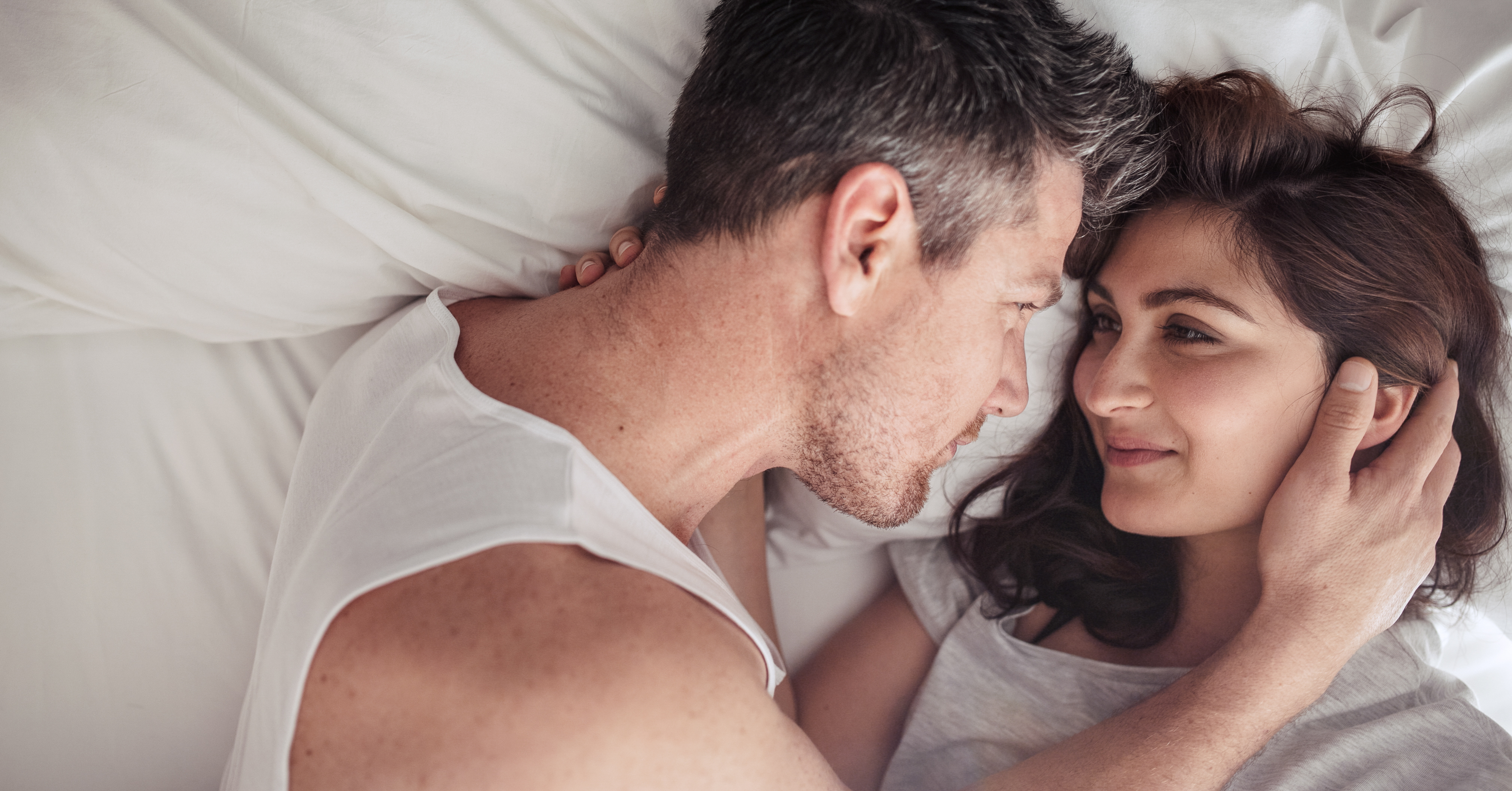 man and woman holding each other in bed, what he wants you to say