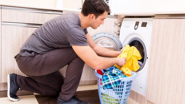 man putting clothes in washing machine laundry folding tips
