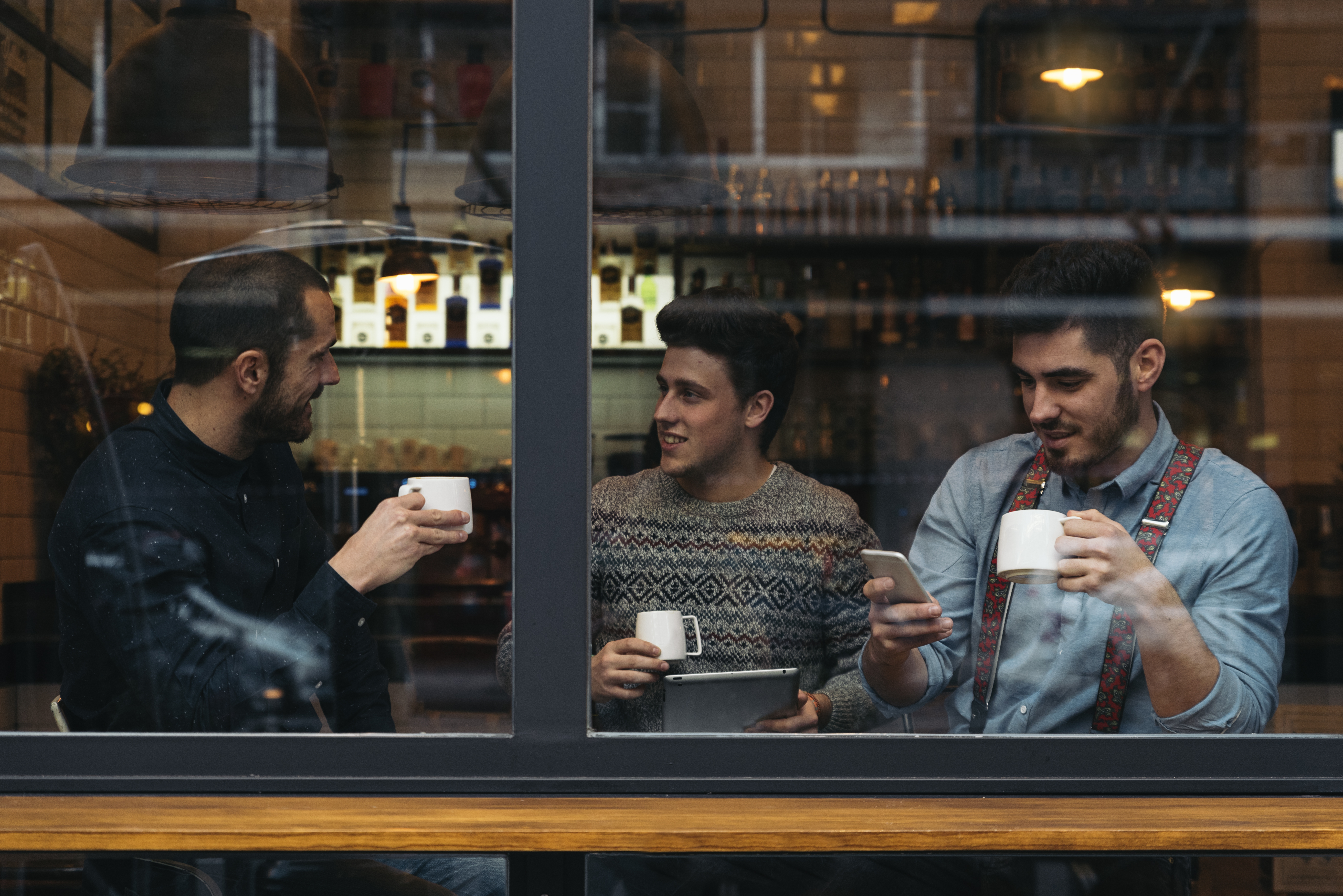 three men sitting in coffee shop window, what he wants you to say