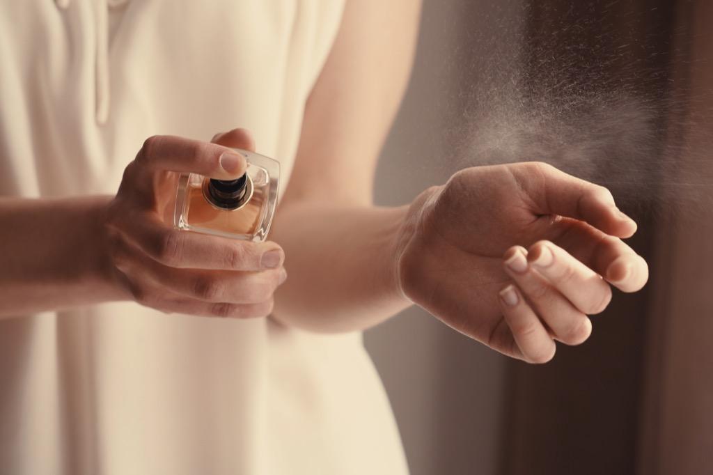 woman spraying perfume floral