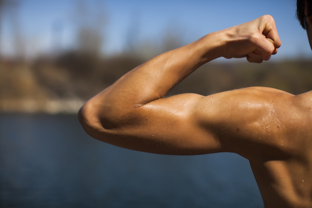 man slexing his arm muscle, ways your body changes after 40