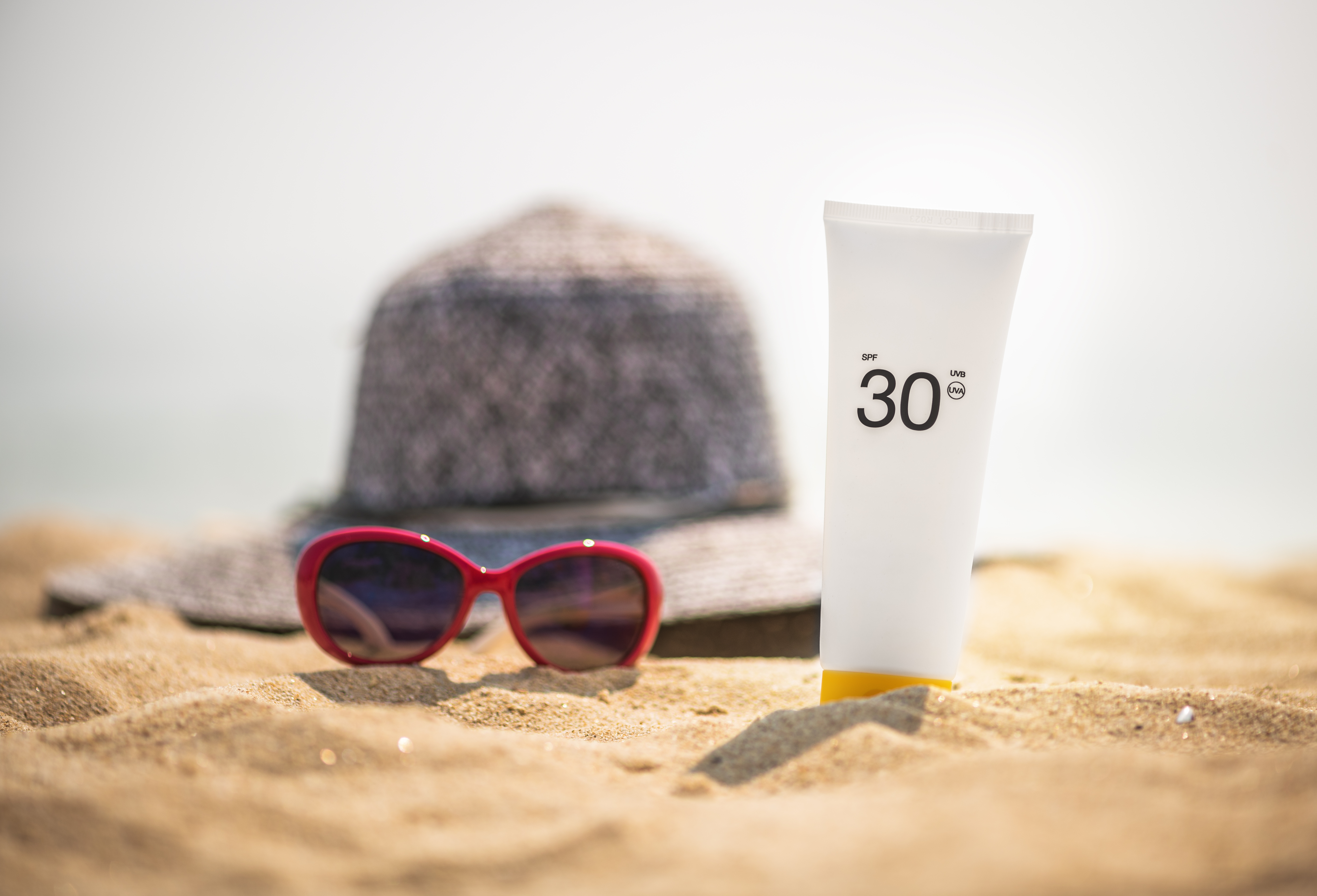 sunglasses and SPF suncreen sitting on a beach, healthy-skin-after-40-spf
