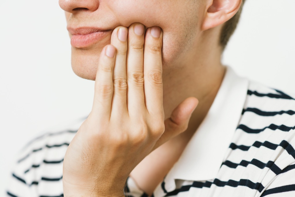 person who has a toothache holding their jaw, ways your body changes after 40