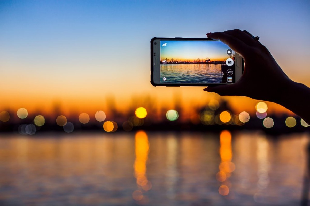 Someone taking a photo of a sunset over water