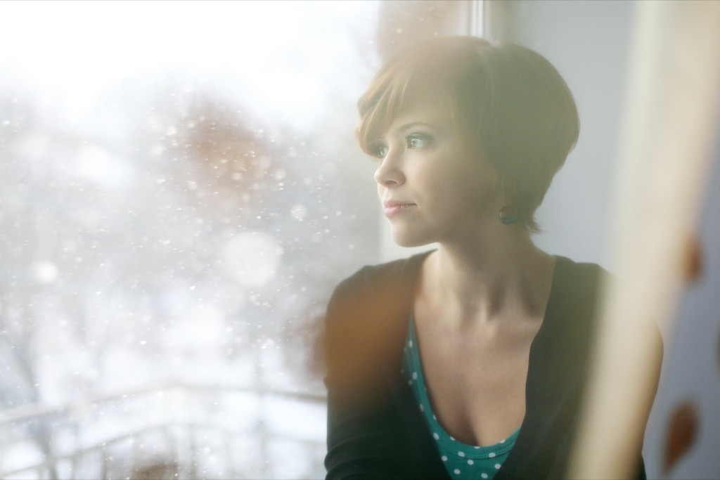 stressed out woman sitting by window stress