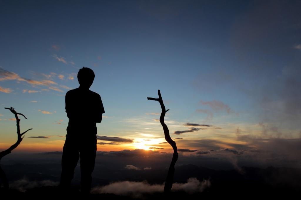 Man staring at sunrise, grateful