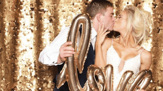 couple holds love balloon while kissing in photo