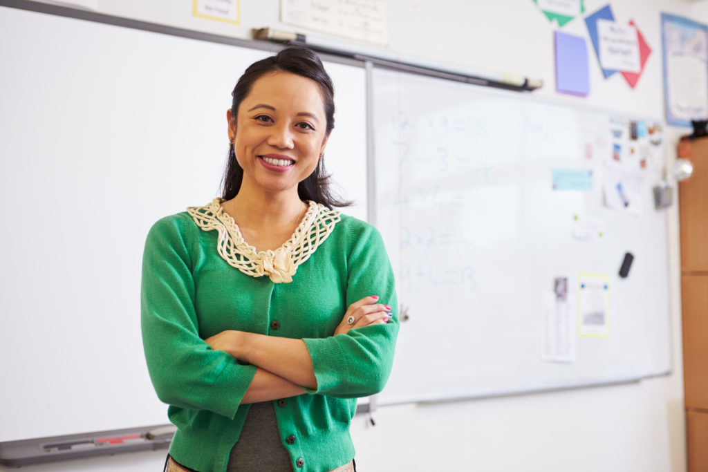 Young female teacher smiling in front of whiteboard in classroom, things you should never say to a teacher