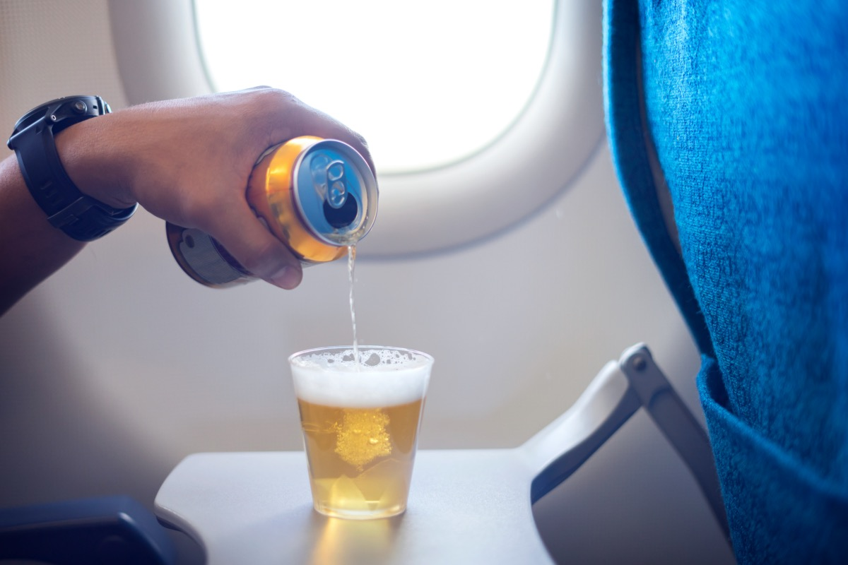 man pouring more beer into his cup on the plane
