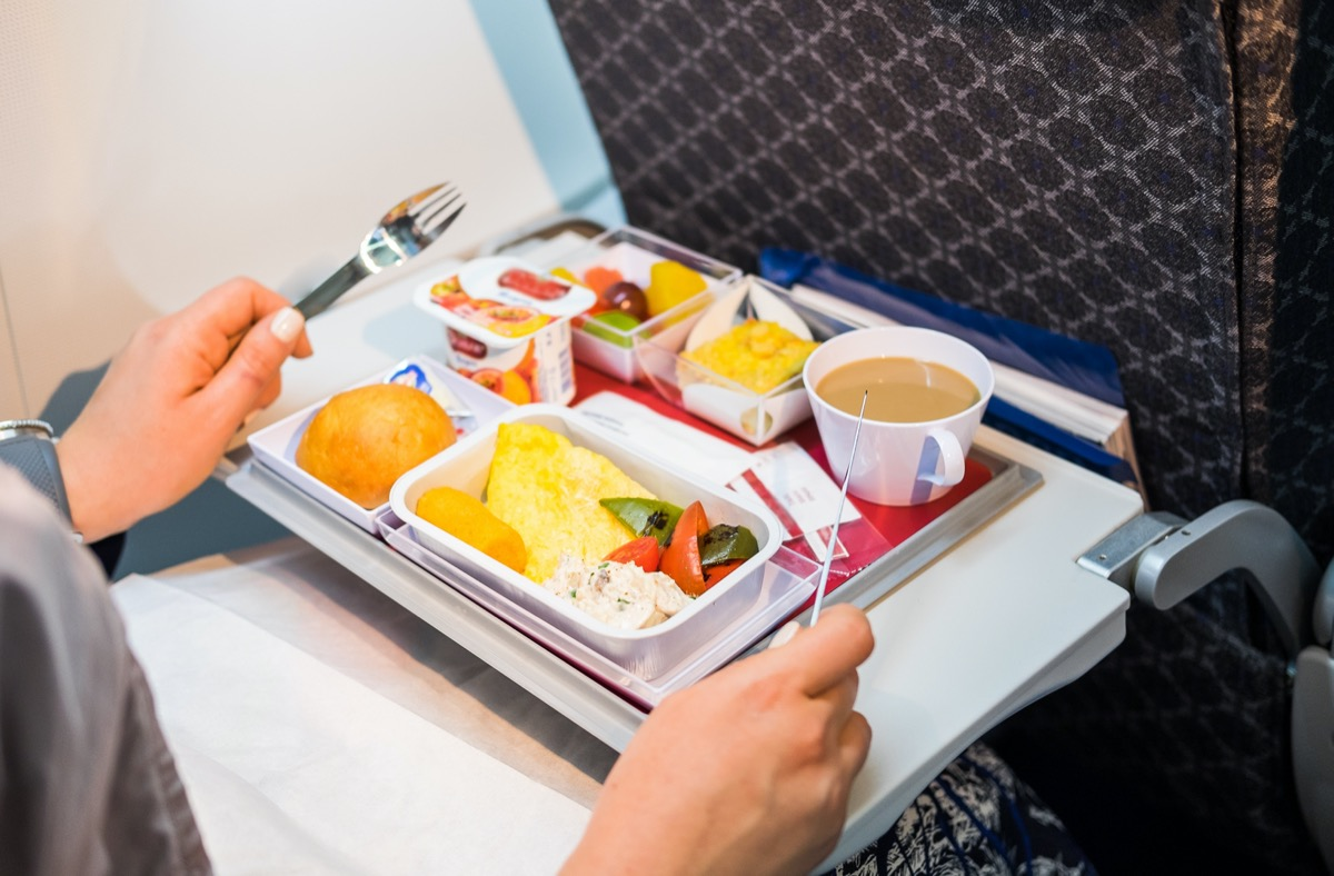 woman getting ready to eat her airplane food