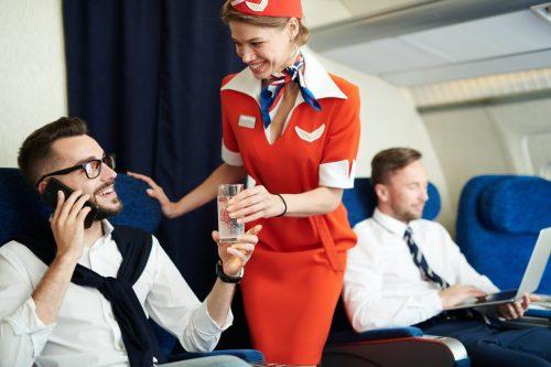 flight attendant helping a first class flyer