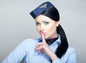 flight attendant shushing with her finger on mouth gesture