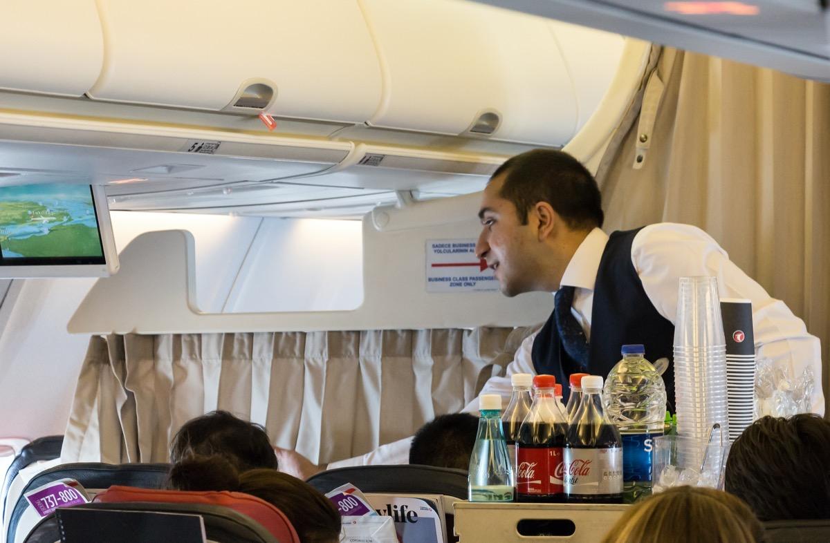 flight attendant giving food to a passenger