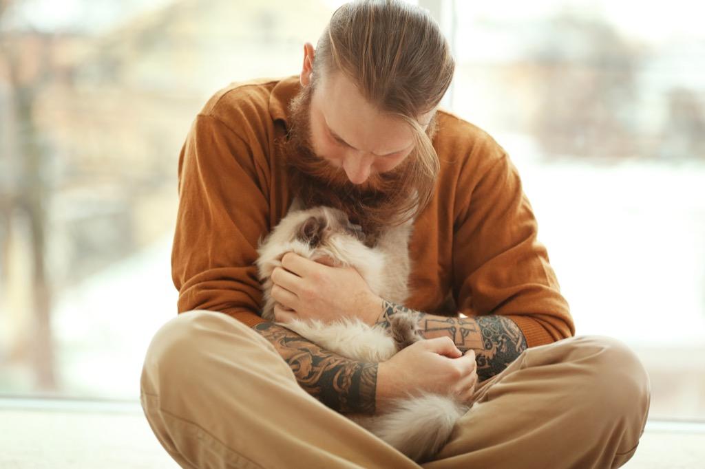 bearded man in orange shirt holding cat