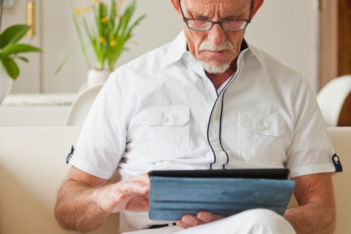older white man using his tablet on couch