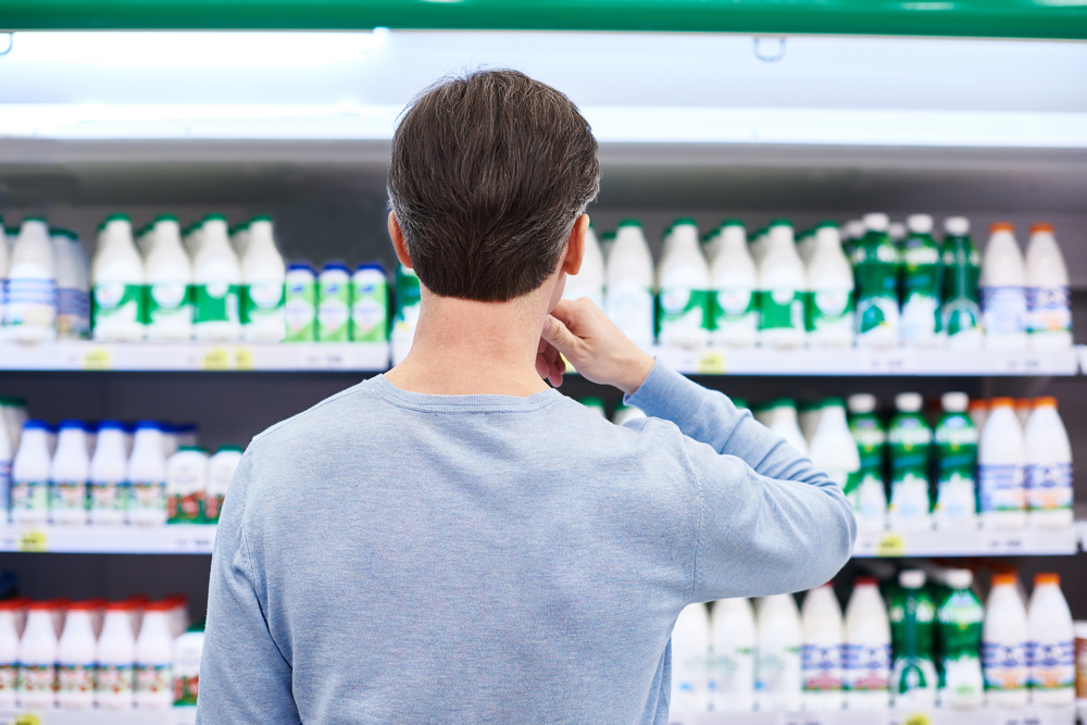 Man buying milk at the store because love