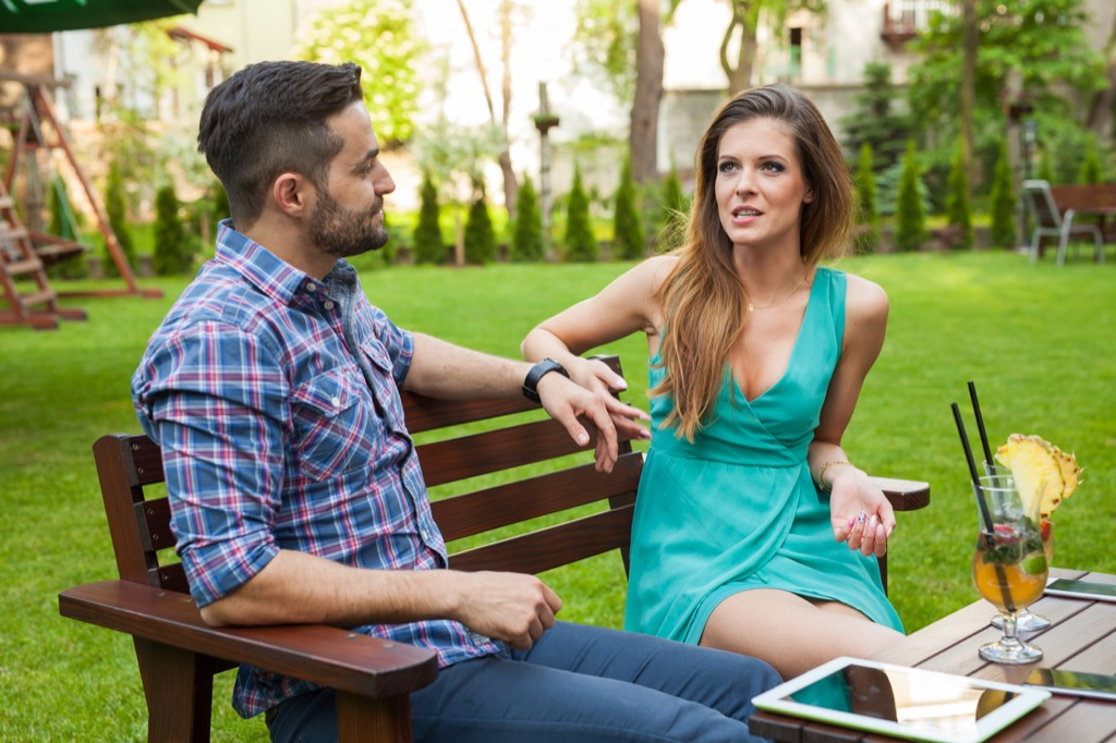 couple arguing in a backyard while drinking a tropical cocktail, signs your husband is cheating