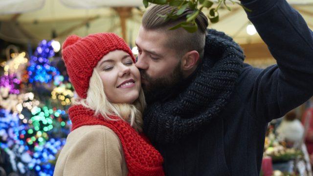 young white couple kissing under mistletoe