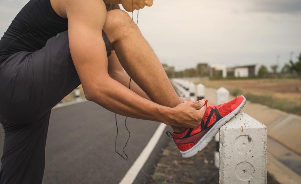 man tying shoes before a morning run