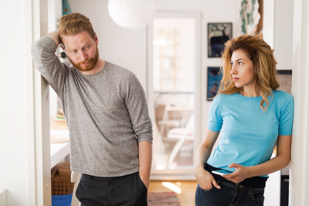 man and woman looking upset and standing in a doorway, signs your husband is cheating