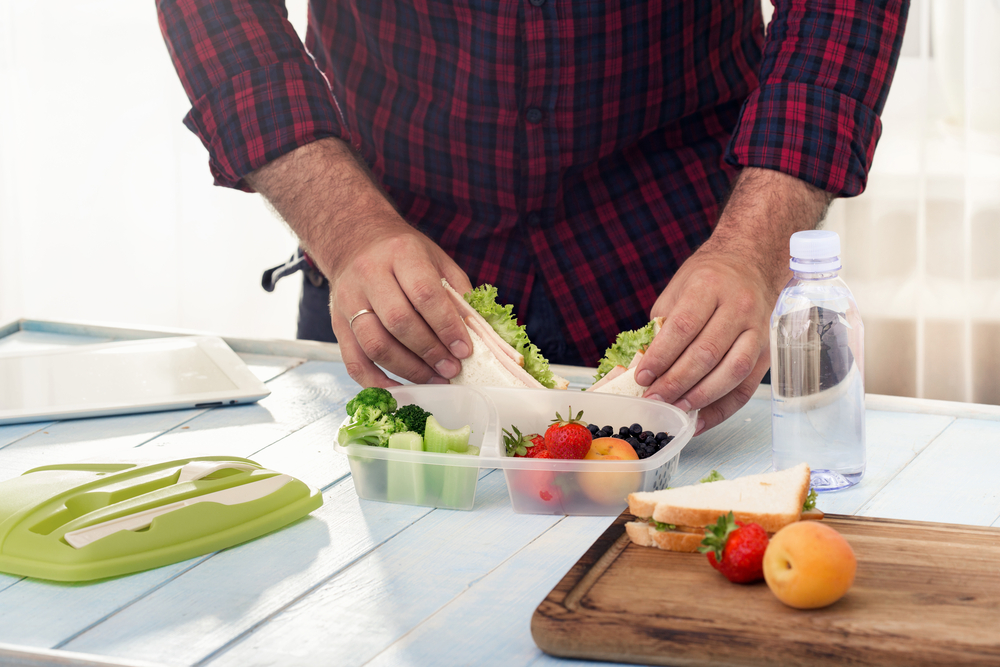 Man making school healthy lunch in the morning in the home kitchen