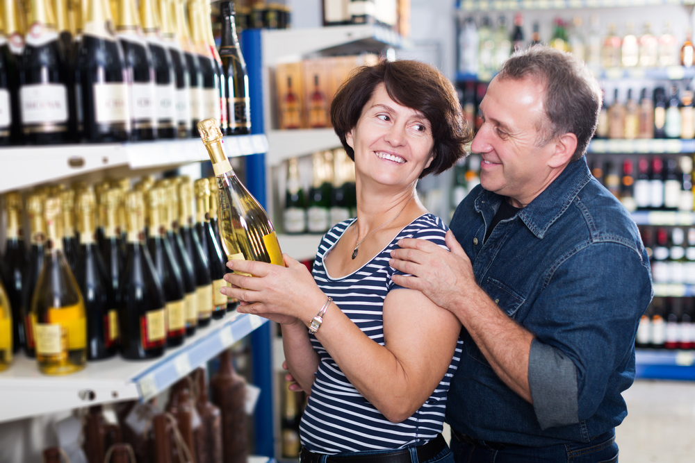 Smiling mature husband and wife selecting wine at the grocery store