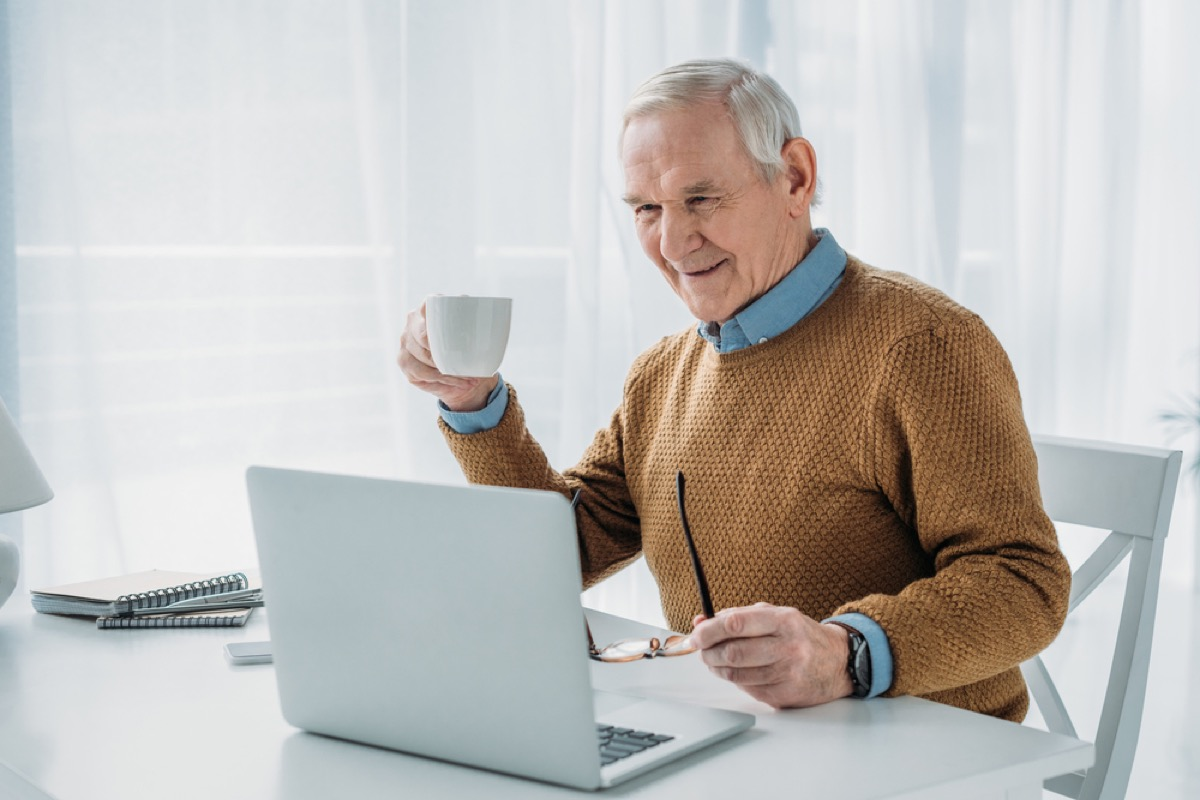 older white man sipping coffee while on his laptop